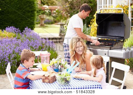 Family Enjoying Outdoor Barbeque In Garden