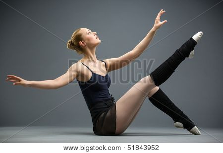 Sideview of dancing on the floor ballerina with her leg up, isolated on white on grey. Concept of elegant art and sportive hobby