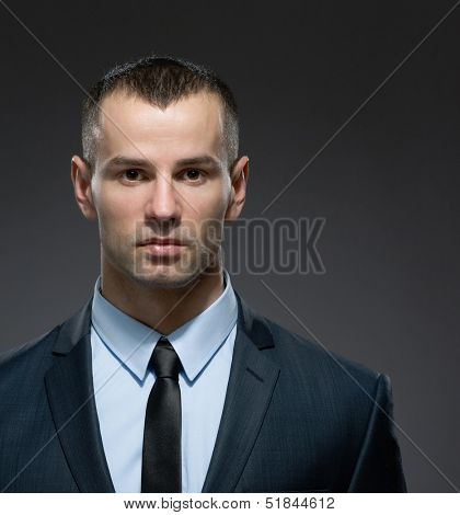 Front view of self-confident manager in dark suit with black tie. Concept of professionalism and success in business