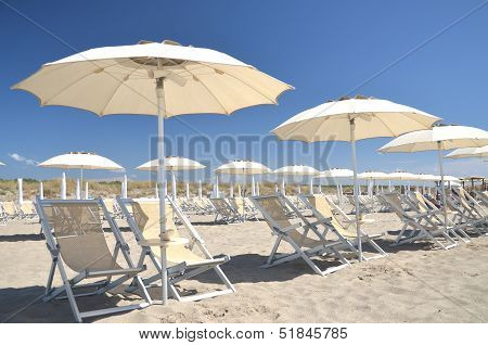 Beach umbrellas and chairs on beautiful beach Marina di Vecchiano nearby Pisa, Tuscany in Italy