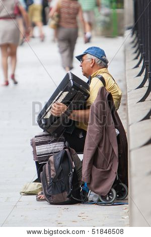 Paris, France - July 27, 2013: An Accordion Player Sitting On A Bridge In Paris And Plays French Son