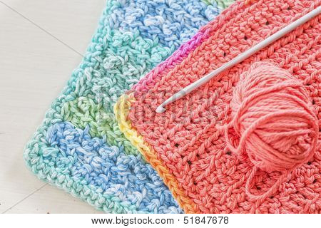 Two hand crotched dishcloths with a crotchet hook and ball of yarn.