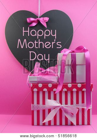 Stack Of Beautiful Pink Stripe And Polka Dot Present Gifts With Heart Shape Blackboard With Happy Mo