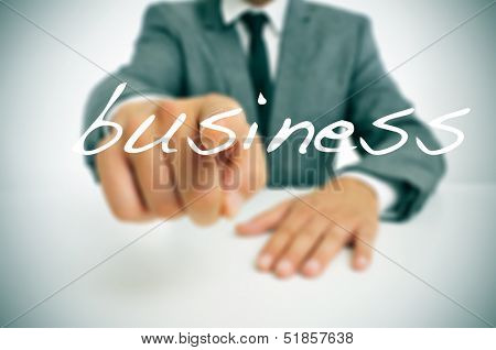 man wearing a suit sitting in a table pointing the finger to the word business written in the foreground