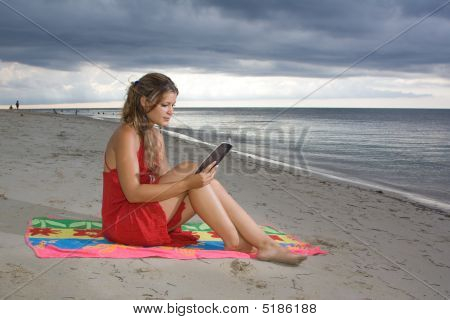Girl With Red Dress Reading A Book In The Beach