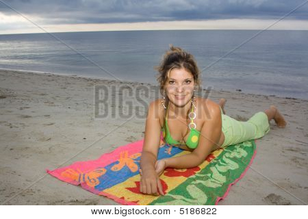 Beautiful Lady Smiling In The Beach, Laying On A Towel