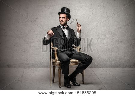 elegant man with cylinder sitting on a chair
