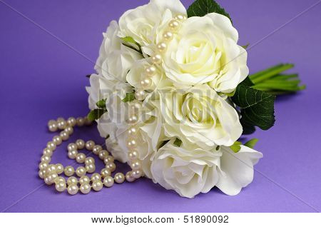 Wedding Bouquet Of White Roses With String Of Pealrs Necklace And Heart Sign With Just Married Messa