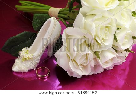 Wedding Bridaal Bouquet Of White Roses On Pink Background With Good Luck Shoe And Wedding Ring.