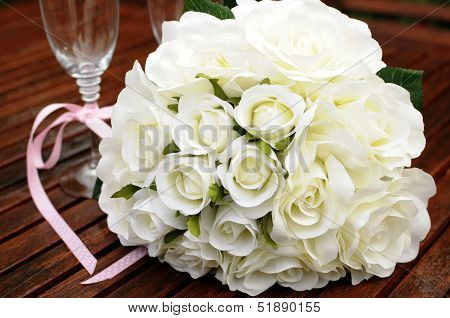 Wedding Bridaal Bouquet Of White Roses With Two Champagne Glasses With Pink Polka Dot Ribbon On Outd