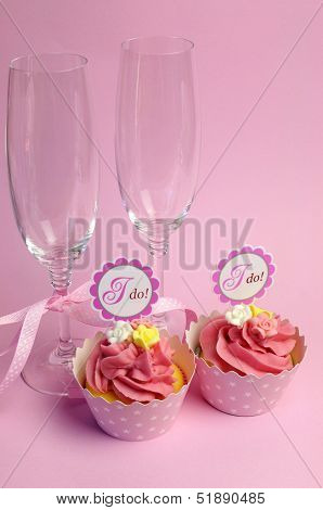 Pink Wedding Cupcakes With I Do Topper Signs - With Champagne Glasses And Polka Dot Ribbon.