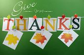 stock photo of pegging  - Give Thanks message spelling in letters hanging from pegs on a line for Thanksgiving greeting in autumn colors with autumn fall leaves - JPG