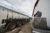 picture of dairy barn  - Truck stand near a barn for the production of milk loading - JPG
