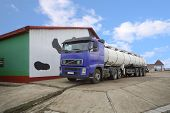 pic of dairy barn  - Truck for the production of milk loading stand near a barn  - JPG