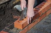 image of bricklayer  - Bricklayer using trowel to tap a brick level - JPG