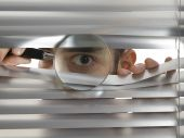 picture of voyeurism  - A man is peeping through the blinds with a magnifying glass - JPG