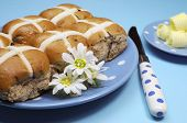 foto of continental food  - Traditional Australian and English Easter Good Friday meal Hot Cross Buns on blue polka dot plate with knife and butter curls on blue background - JPG