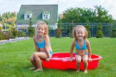 Two Little Sisters Sitting In Their Yard In Small Pool