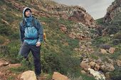 stock photo of survival  - Adventure man hiking wilderness mountain with backpack - JPG