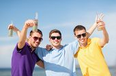 summer, holidays, vacation, happy people concept - group of friends having fun on the beach with bot