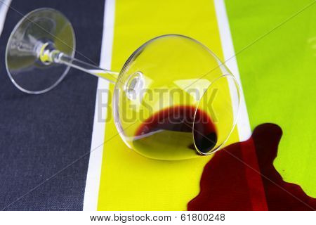 Overturned glass of wine on table close-up