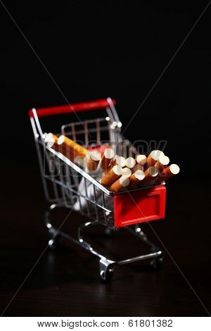 Cigarettes in shopping cart on wooden table on dark background