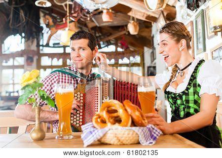 Bavarian man playing folk music for woman wearing dirndl
