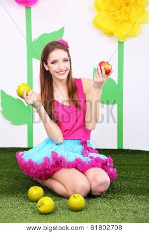 Beautiful young woman in petty skirt with apples on decorative background