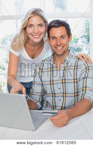 Smiling young couple doing online shopping through laptop and credit card at home