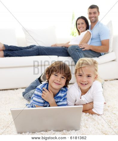 Children Playing With A Laptop And Parents Lying On Sofa