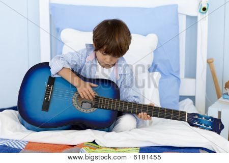 Little Boy Playing Guitar In Bed