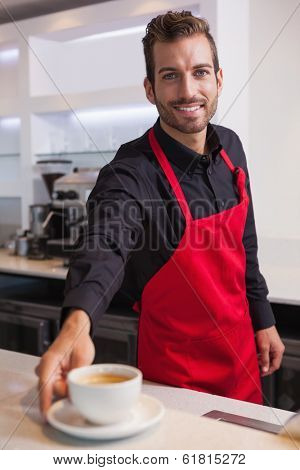 Smiling young barista putting cup of coffee down on counter in a cafe