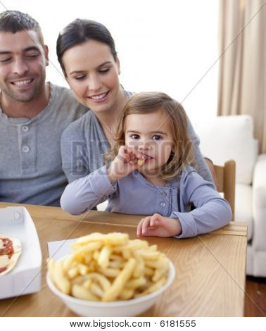 Little Girl Eating Fries And Pizza At Home