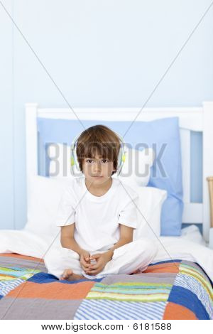 Sad Little Boy Listening To Music In Bed