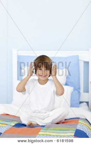 Little Boy Listening To Music In His Bed