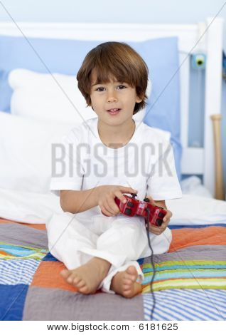 Boy Sitting In Bed Playing Videogames