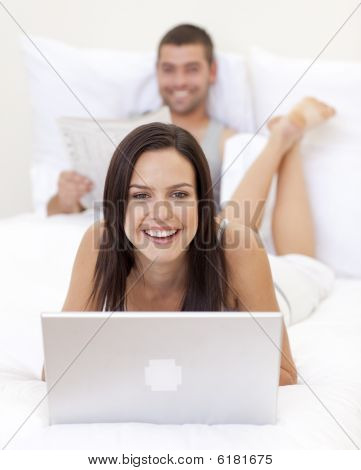 Woman Using A Laptop And Man Reading