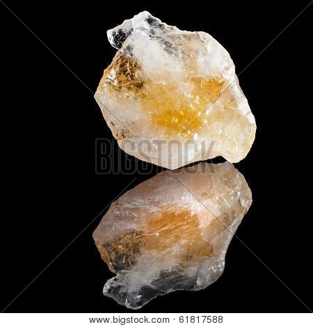 Yellow Citrine rock with reflection on black surface background