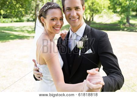 Portrait of happy bride and groom dancing together in garden