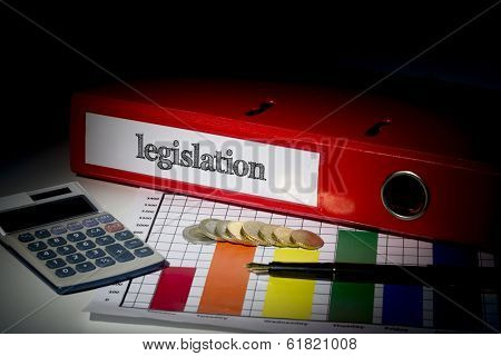 The word legislation on red business binder on a desk