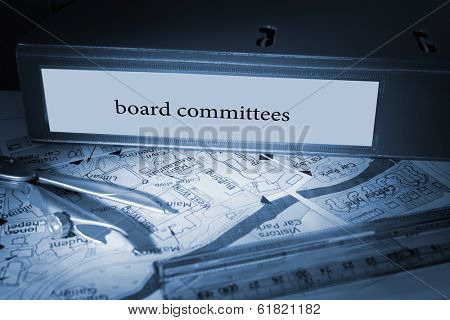 The word board committees on blue business binder on a desk