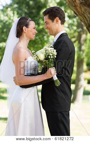 Side view of happy newly wed couple looking at each other in garden