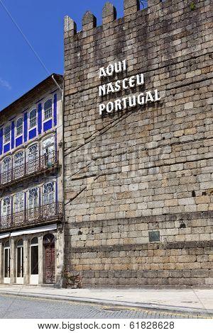 The iconic Guimaraes Castle Wall with the inscription Aqui Nasceu Portugal (Portugal was born here). Guimaraes, Portugal. Unesco World Heritage Site.