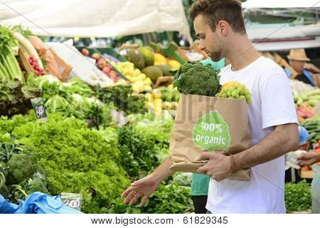 Male consumer at an open street market carrying a shopping paper bag with a 100% organic certified label full of fruit and vegetables.