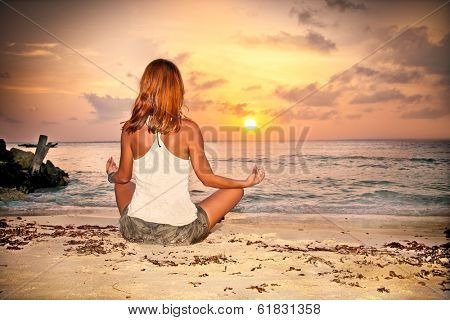 A relaxed sexy young brunette woman sitting on a deserted tropical beach at sunset