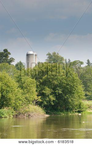 Looking Across A River At Grain Silos