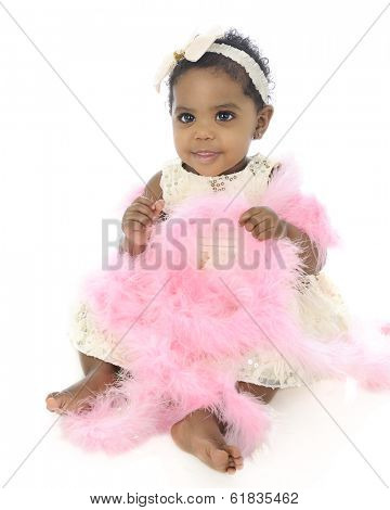 A beautiful, dressed up baby girl happily sitting with her lap full of a pink boa.  On a white background.