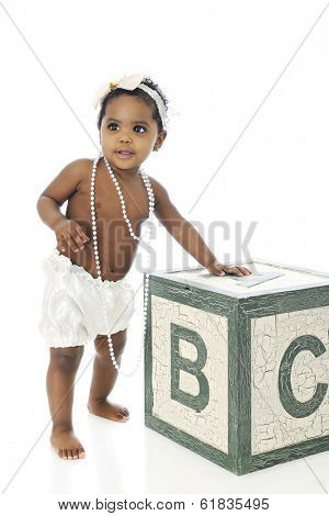 A beautiful baby girl standing with support.  She wears a white hair bow, long strands of beads and silky bloomers.  On a white background.