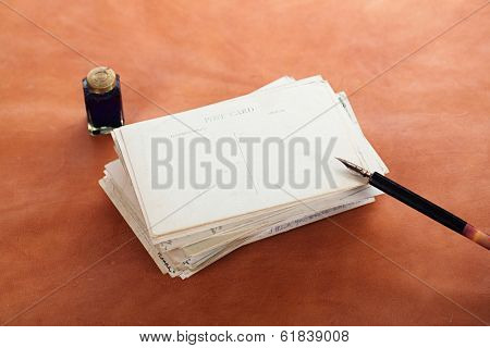 pile of vintage post cards with  ink pen, inkpot on leather table, retro colors
