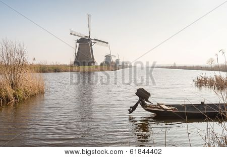 Row Of Windmills And A Small Boat With Outboard Engine